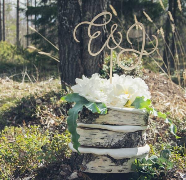 Koivukakku ja kaunis vanerinen koriste jossa hääpärin etunimien ensimmäiset kirjaimet.