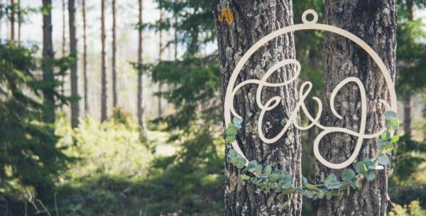 Vanerinen hääkranssi eukalyptuksella koristeltuna kahden puun välissä. Taustalla näkyy metsäaukio.