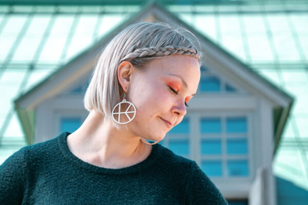 Lettihiuksinen nainen silmät kiinni hymyillen Kalevan Navetta rakennuksen edessä korvissaan logo korvakorut.