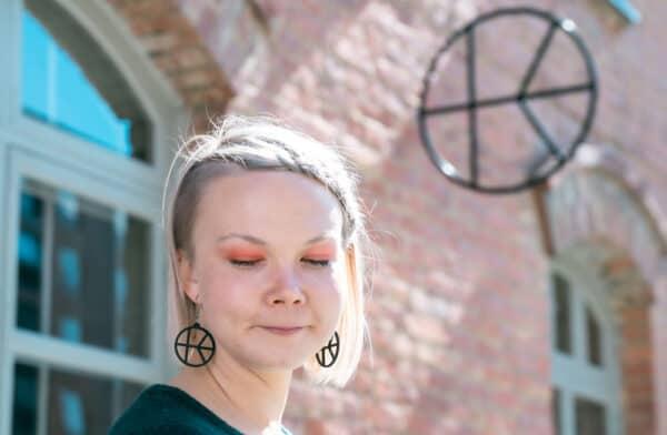 Hymyilevä malli mustat Kalevan Navetta korvakorut korvissaan. Taustalla näkyy metallinen logo tiiliseinässä.