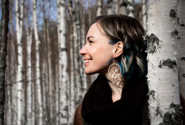 Hymyilevä nainen koivun vieressä vaneriset Oksat korvakorut korvissa.