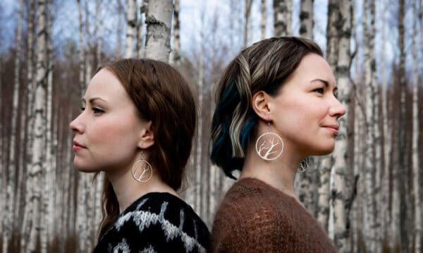 Kaksi naista koivumetsässä selkä selkää vasten katsomassa kaukaisuuteen Oksat korvakorut korvissa,