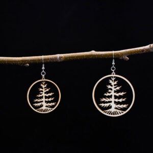 Kaksi ympyrän muotoista vanerikorvakorua, joissa on kuusi-kuvio.