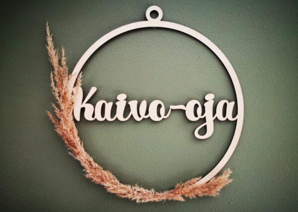 Heinällä koristeltu koivuvanerinen ovikranssi Kaivo-oja tekstillä vihreää seinää vasten.