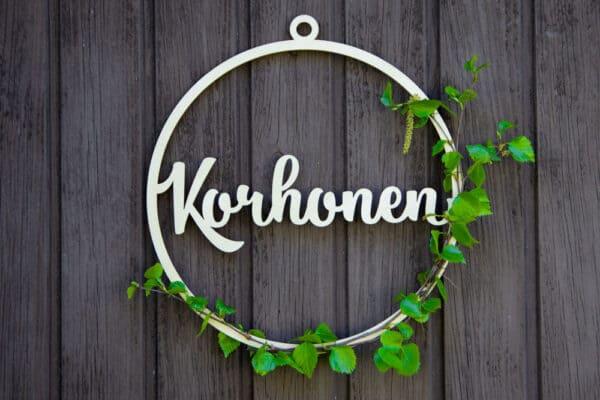 Koivunoksalla koristeltu vanerinen kranssikehys jossa lukee sukunimi Korhonen.