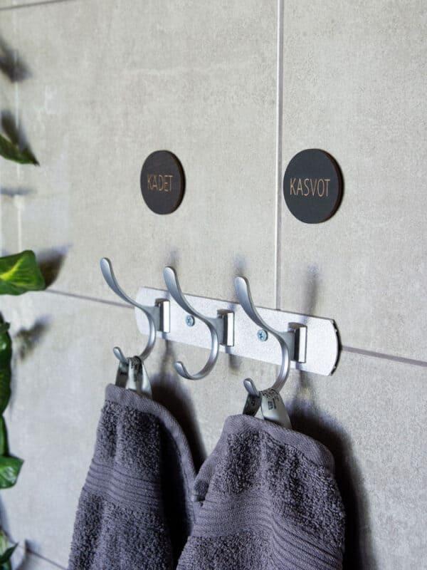Mustat koivuvaneriset pyyhemerkit joissa lukee kädet ja kasvot kylpyhuoneen pyyhenaulakon yläpuolella.