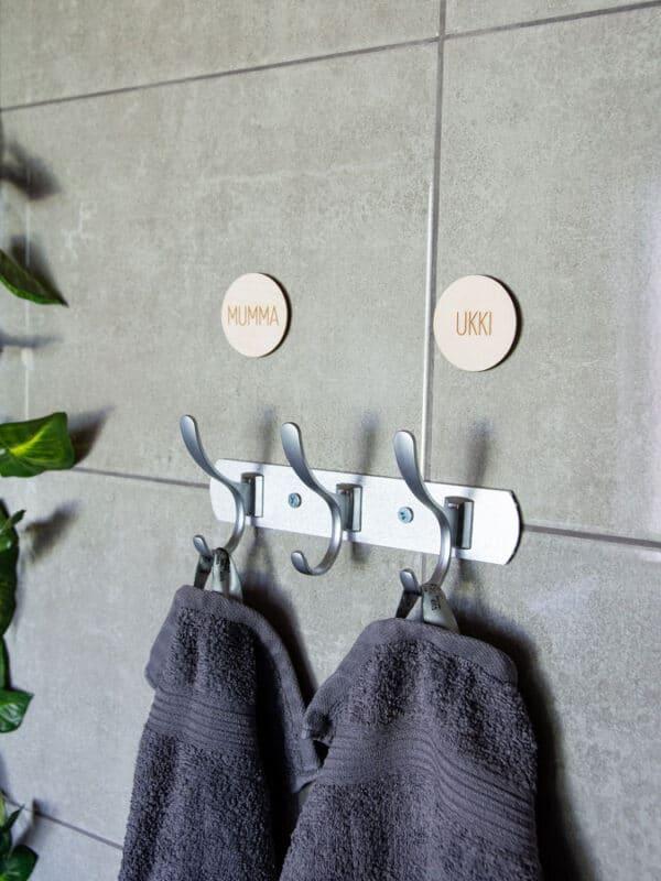 Koivuvaneriset pyyhemerkit joissa lukee kädet ja kasvot kylpyhuoneen pyyhenaulakon yläpuolella.
